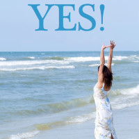 woman-at-beach-handsup_web